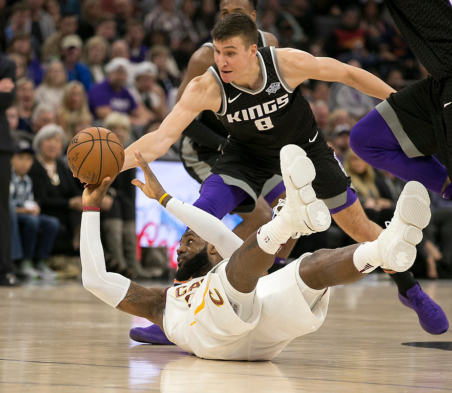. Cleveland Cavaliers forward LeBron James, left, turns the ball over as he goes to the floor against Sacramento Kings guard Bogdan Bogdanovic during the first quarter of an NBA basketball game, Wednesday, Dec. 27, 2017, in Sacramento, Calif. (AP Photo/Rich Pedroncelli)