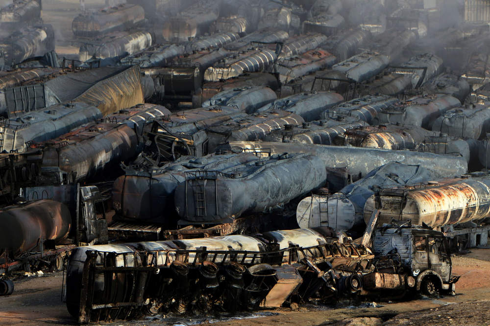 . Burned-out fuel trucks are seen following an overnight attack by Taliban militants in Chawk-e-Arghandi on outskirts of the Afghan capital Kabul on July 5, 2014. Taliban militants set fire to dozens of fuel trucks on the outskirt of Kabul, officials said. The fire triggered by a sticky bomb set a blaze dozens of fuel tankers waiting to enter the city in Chawk-e-Arghandi parking lot west of Afghan capital overnight. (WAKIL KOHSAR/AFP/Getty Images)