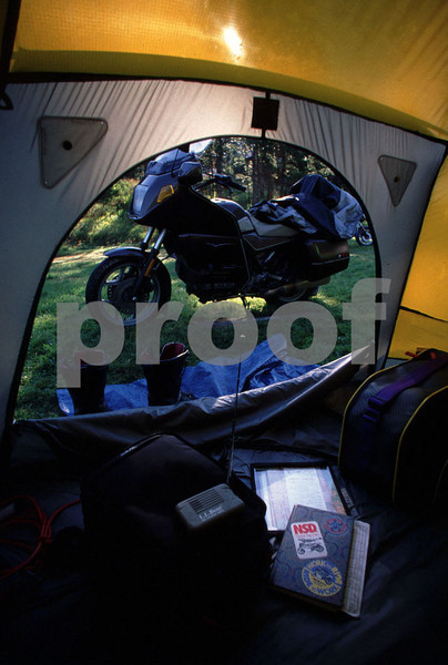 Motorcycle camping on a BMW bike complete with North Face tent, weather radio, diary, tank bag, luggage liner, and boots