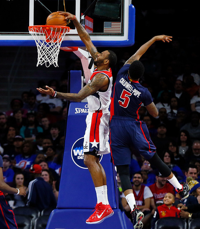 . Washington Wizards forward Rasual Butler, left, dunks against Detroit Pistons guard Kentavious Caldwell-Pope (5) in the first half of an NBA basketball game in Auburn Hills, Mich., Sunday, Feb. 22, 2015. (AP Photo/Paul Sancya)