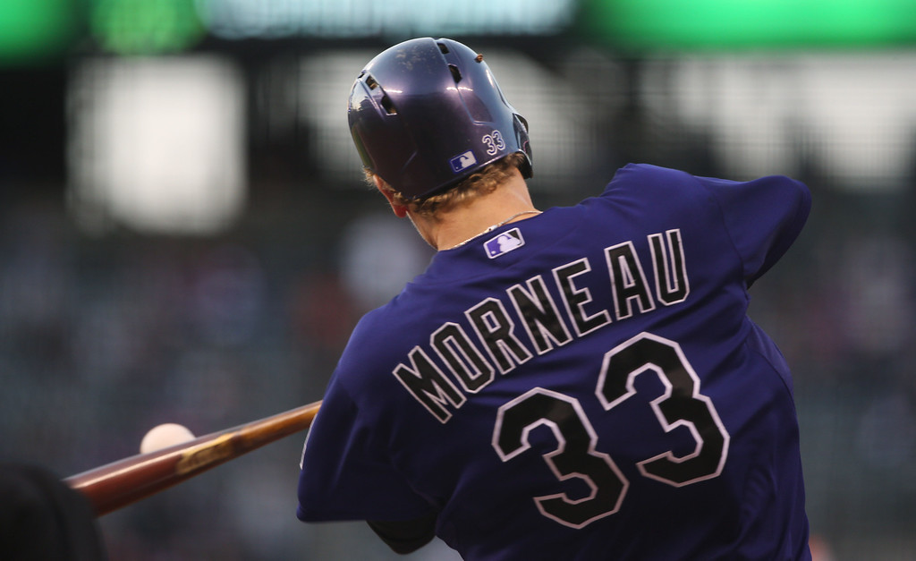 . Colorado Rockies\' Justin Morneau connects for a double against the San Francisco Giants in the first inning of a baseball game in Denver on Monday, April 21, 2014. (AP Photo/David Zalubowski)