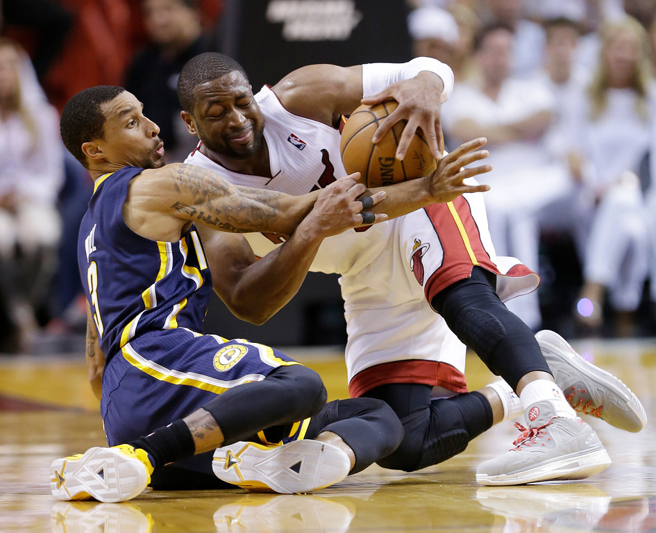. Indiana Pacers guard George Hill, left,  and Miami Heat guard Dwyane Wade, fight over a loose ball during the first half of Game 4 in the NBA basketball Eastern Conference finals playoff series, Monday, May 26, 2014, in Miami. (AP Photo/Wilfredo Lee)