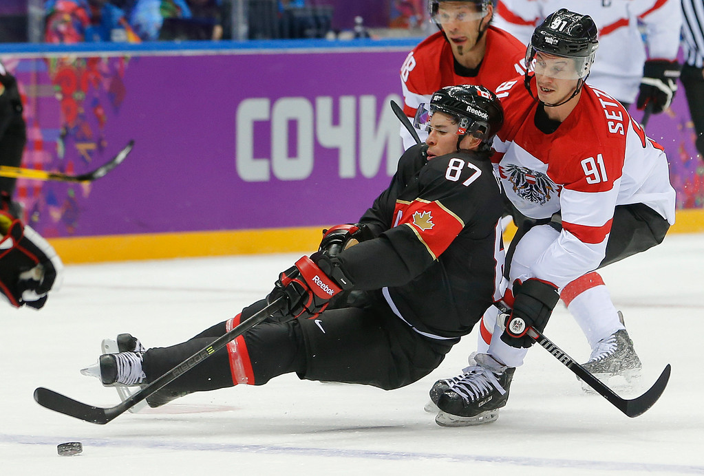 . Canada forward Sidney Crosby loses his footing against Latvia forward Ronalds Kenins in the first period of a men\'s ice hockey game at the 2014 Winter Olympics, Friday, Feb. 14, 2014, in Sochi, Russia. (AP Photo/Mark Humphrey)