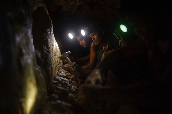 . Gold miners use a sledgehammer to free raw ore from the tunnel walls before hauling it to processing stations on the surface, on April 22, 2014 in Pinut-An, Philippines. (Photo by Luc Forsyth/Getty Images)