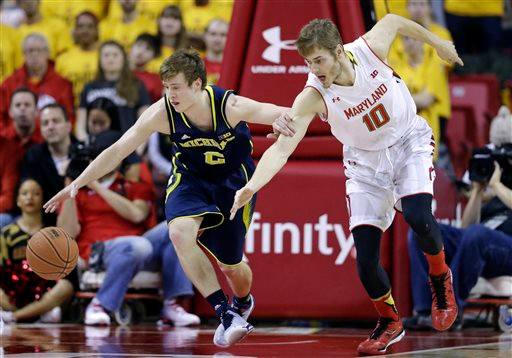 . Michigan guard Spike Albrecht, left, holds back Maryland guard/forward Jake Layman, as he reaches for the ball in the first half of an NCAA college basketball game, Saturday, Feb. 28, 2015, in College Park, Md. (AP Photo/Patrick Semansky)