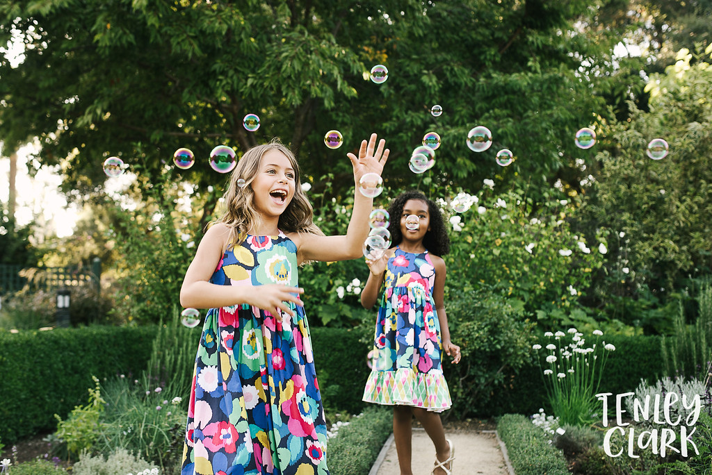 Playful kids fashion editorial-style commercial brand shoot with two girls playing in a garden for Gold Magnolia kids clothing boutique by Tenley Clark Photography. Models: Sofia and Olivia. Girls chasing bubbles