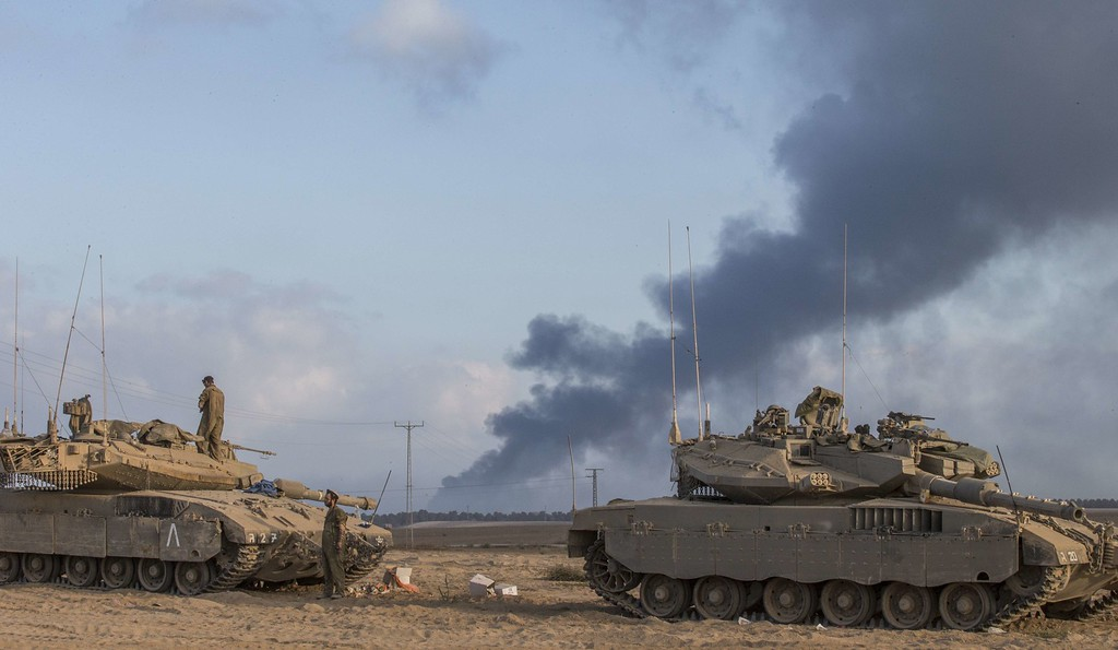 . Israeli Merkava tanks are seen at an army deployment area near the border with the Gaza Strip, on July 31, 2014, as smoke billows from the coastal Palestinian enclave. Israel mobilised 16,000 additional reservists today to bolster forces fighting in Gaza as Washington gave its ally the go-ahead to raid stocks of emergency US weapons stored on Israeli soil.  AFP PHOTO/JACK GUEZ/AFP/Getty Images
