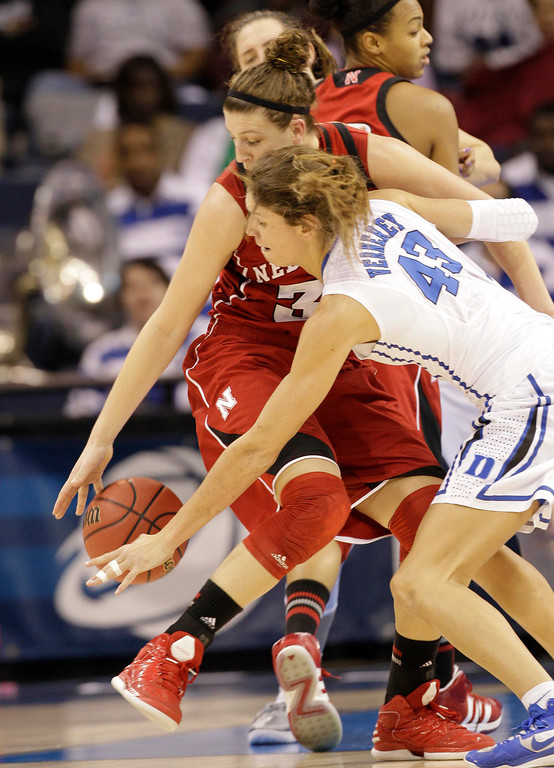 . Nebraska forward Jordan Hooper, left, struggles to control the ball as Duke center Allison Vernerey (43) close in during a regional semi-final of the NCAA college basketball tournament Sunday  March 31, 2013, in Norfolk, Va.  (AP Photo/Steve Helber)
