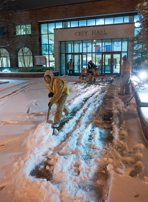 . Fayetteville Parks and Recreation workers shovel the city hall sidewalk during the early morning hours of Wednesday Jan. 29, 2014. (AP Photo/The Fayetteville Observer, Johnny Horne)