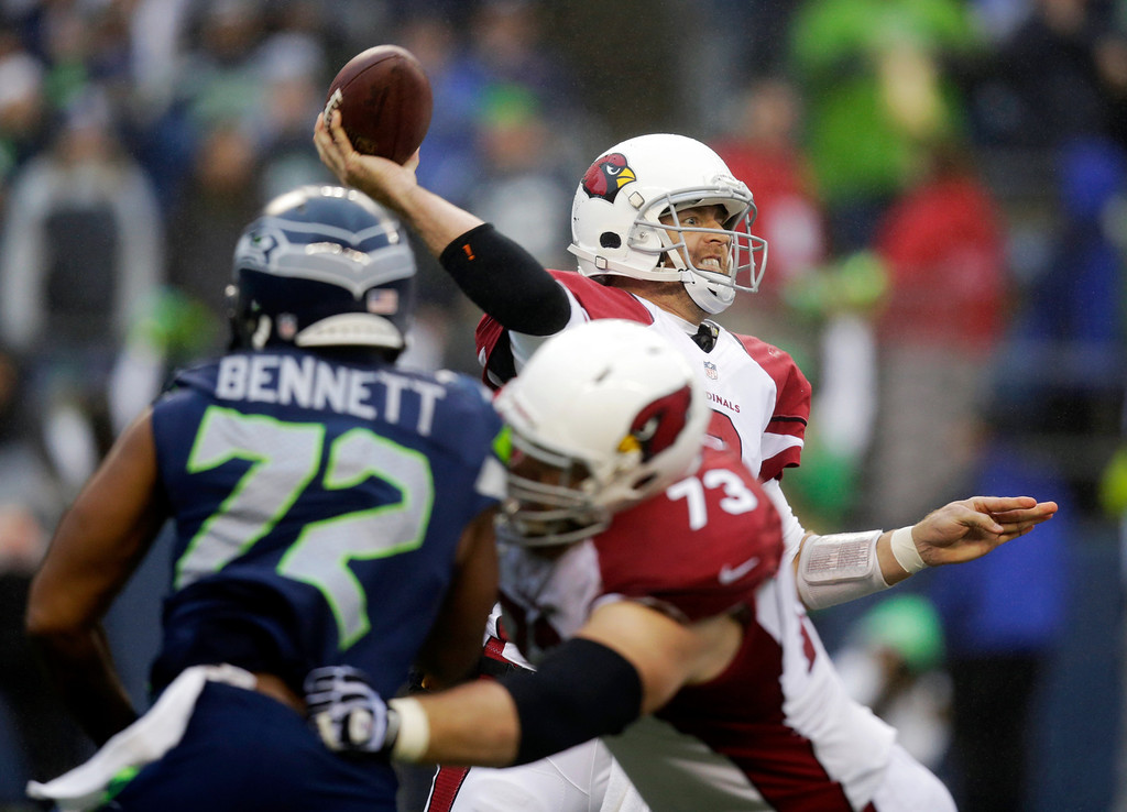 . Arizona Cardinals quarterback Carson Palmer passes the ball as Cardinals tackle Eric Winston (73) blocks Seattle Seahawks defensive end Michael Bennett (72) in the second half of an NFL football game, Sunday, Dec. 22, 2013, in Seattle. The Cardinals won 17-10. (AP Photo/Stephen Brashear)