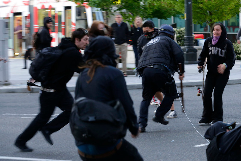 . A Seattle Police officer is tripped up by a string held by protesters as he runs at them with his baton during a May Day march that began as an anti-capitalism protest and turned into demonstrators clashing with police, Wednesday, May 1, 2013, in downtown Seattle. (AP Photo/Ted S. Warren)