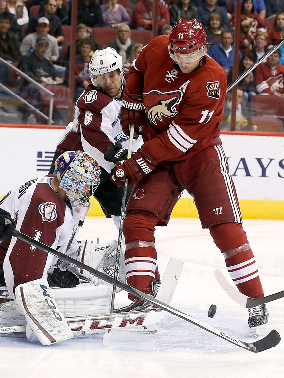 . Phoenix Coyotes\' Martin Hanzal (11), of Czech Republic, battle with Colorado Avalanche\'s Jan Hejda (8), of Czech Republic, for the puck in front of Avalanche goalie Semyon Varlamov (1), of Russia, during the second period of an NHL hockey game Thursday, Nov. 21, 2013, in Glendale, Ariz. (AP Photo/Ross D. Franklin)