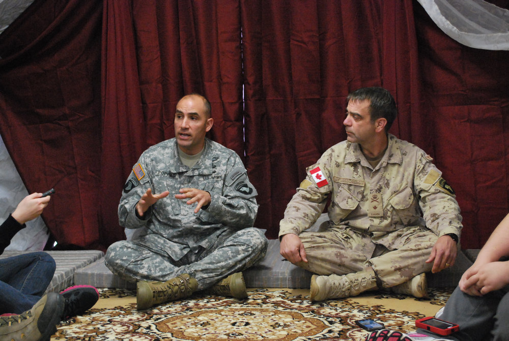 . U.S. Army Col. Andrew Poppas, left, and Canadian Brig. Gen. Dave Corbould, right, speak with reporters inside a tent at Fort Campbell, Ky., on Friday, Dec. 7, 2012. The 101st Airborne Division is training with international military partners in preparation for an upcoming deployment to Afghanistan this winter. (AP Photo/Kristin M. Hall)
