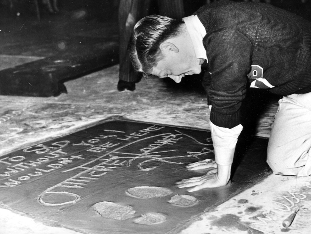. Mickey Rooney, 18-year-old film actor, singer and dancer, plants his hands into the cement next to his footprint and signature in the forecourt of Grauman\'s Theater on Hollywood Boulevard during induction ceremonies in Hollywood, Ca., on Oct. 19, 1938.  (AP Photo)