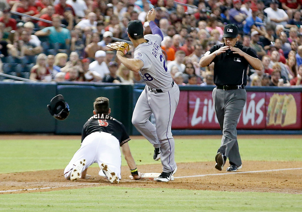 . Colorado Rockies\' third baseman Nolan Arenado looks for a call from the third base umpire Manny Gonzalez after knocking off the helmet of the Arizona Diamondbacks\' Ender Inciarte in the third inning of a baseball game, Saturday, Aug. 9, 2014, in Phoenix. Inciarte was safe going back to third. (AP Photo/Darryl Webb)