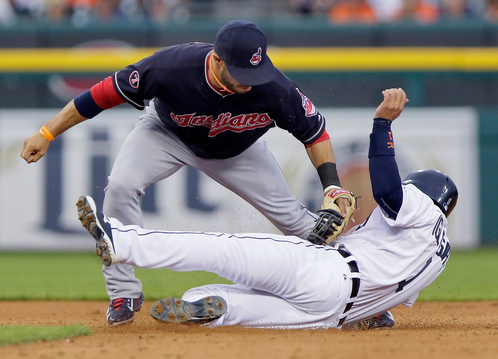 . Detroit Tigers\' Jose Iglesias is tagged out by Cleveland Indians shortstop Mike Aviles while trying to steals second base during the fifth inning of a baseball game Friday, June 12, 2015, in Detroit. (AP Photo/Duane Burleson)