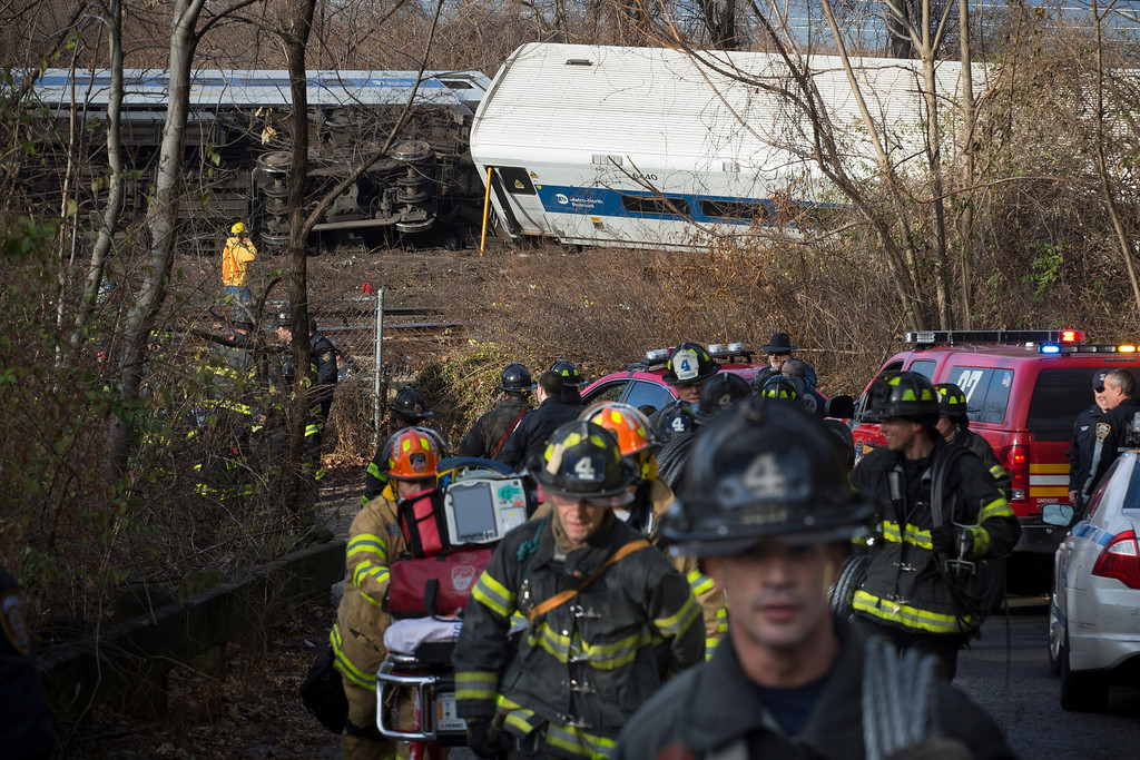 . Firefighters respond to the scene of a Metro-North passenger train derailment in the Bronx borough of New York Sunday, Dec. 1, 2013. The train derailed on a curved section of track in the Bronx on Sunday morning, coming to rest just inches from the water and causing multiple fatalities and dozens of injuries, authorities said. Metropolitan Transportation Authority police say the train derailed near the Spuyten Duyvil station. (AP Photo/John Minchillo)