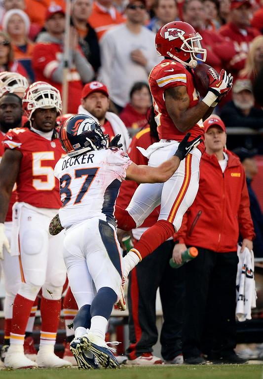 . Kansas City Chiefs cornerback Marcus Cooper (31) intercepts a pass intended for Denver Broncos wide receiver Eric Decker (87) during the second quarter December 1, 2013 at Arrowhead Stadium.  (Photo by John Leyba/The Denver Post)