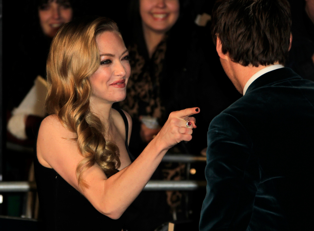 Description of . Amanda Seyfried points at Eddie Redmayne as they arrive on the red carpet for the World Premiere of 'Les Miserables' at a central London cinema in Leicester Square, Wednesday, Dec. 5, 2012. (Photo by Joel Ryan/Invision/AP)