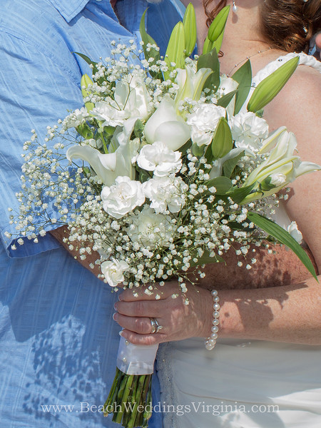 mixture of whites: lilies, roses, spray roses, carnations & baby's breath. Stems tied in white ribbon