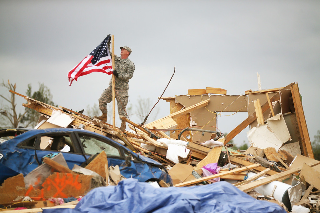 . Arkansas National Guard Staff Sgt. Skipper Smith hangs an American flag on a pole at the site of a home that was destroyed when a tornado hit the area April 29, 2014 in Vilonia, Arkansas.  (Photo by Mark Wilson/Getty Images)