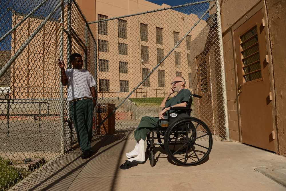 . While having a good day, Robert Bryan, right, decides he feels well enough to go out to the prison yard for the first time in two months, November 08, 2012.  He rarely left his infirmary bed due to his battle with liver cancer. Bryan kicked off his sandals in the sunlight while he spoke to his friend, caretaker and fellow inmate Wayne Rose. (Photo By RJ Sangosti/The Denver Post)