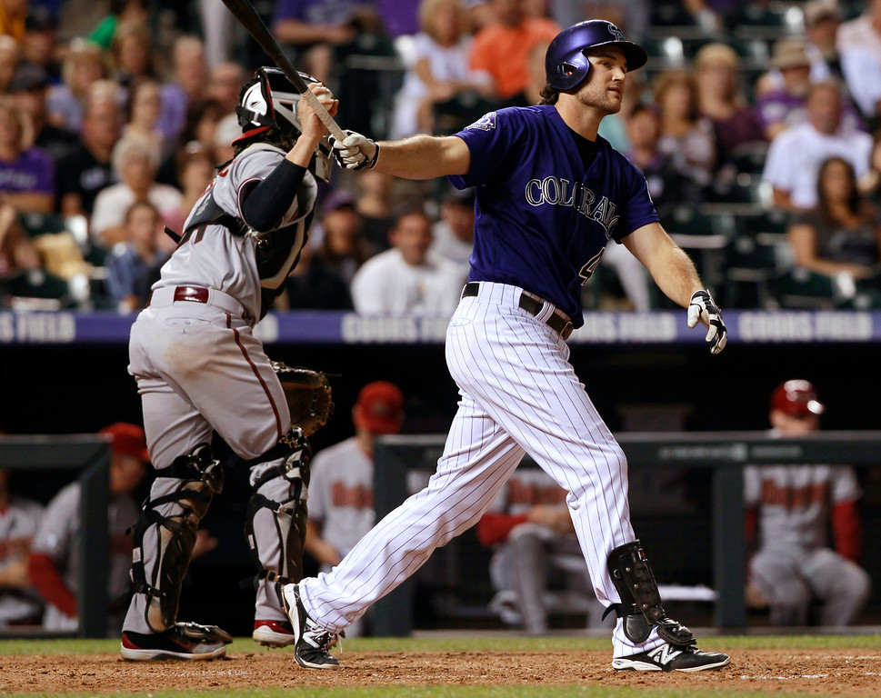 . Colorado Rockies pinch-hitter Ryan Wheeler, right, reacts as he strikes out while swinging as Arizona Diamondbacks catcher Tuffy Gosewisch heads to the dugout at the end of the sixth inning of a baseball game in Denver on Saturday, Sept. 21, 2013. (AP Photo/David Zalubowski)