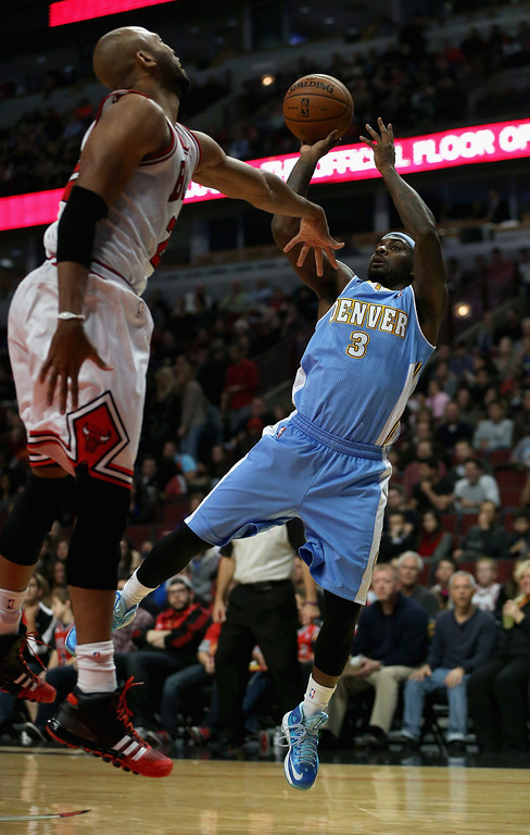 . Ty Lawson #3 of the Denver Nuggets shoots against Taj Gibson #22 of the Chicago Bulls during a preseason game at the United Center on October 25, 2013 in Chicago, Illinois.  (Photo by Jonathan Daniel/Getty Images)