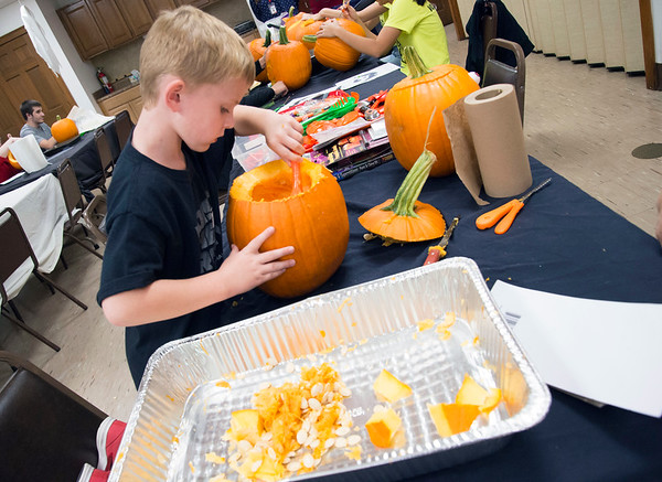10/14/19 Wesley Bunnell | StaffrrVolunteers, many of them high school students and members of the Interact Club, carved pumpkins for the upcoming lighted jack-o-lantern trail walk coming up this Friday October 18th and October 19th at Hungerford Nature Center. Five year old Patrick McCourt helps scoop the seeds from a pumpkin to be carved.