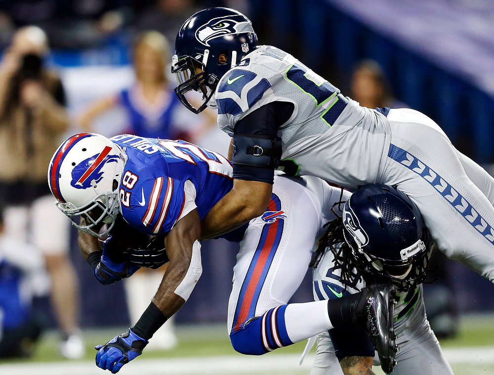 . Buffalo Bills running back C.J. Spiller (28) is tackled by Seattle Seahawks free safety Earl Thomas (29) and outside linebacker K.J. Wright (50) during the first half of an NFL football game, Sunday, Dec. 16, 2012, in Toronto. (AP Photo/Mike Groll)