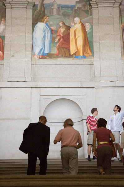 """Vistors at El Escorial main staircase examining the fresco painting and the large staircase itself. The staircase was made by Giambattista Castello, called """"Il Bergamasco"""" (16th century). The fresco paintings are a work by the Spanish painter Lucas Jordan (17th century)."""