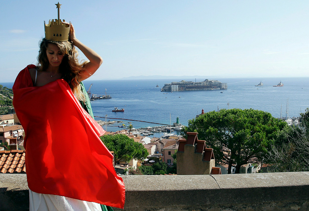 . Christine Sanikidze, from Monte Carlo, wearing a crown and an outfit with the colors of the Italian flag, prepares to pose for a photo shoot session as the Costa Concordia cruise ship, is towed away from the tiny Tuscan island of Isola del Giglio, Italy, Wednesday, July 23, 2014. After more than two years since it slammed into a reef along the coastline of Isola del Giglio the wreck has begun its last journey, to the Italian port of Genoa, where it will be scrapped. 32 people died in the incident, one body is still missing. (AP Photo/Gregorio Borgia)
