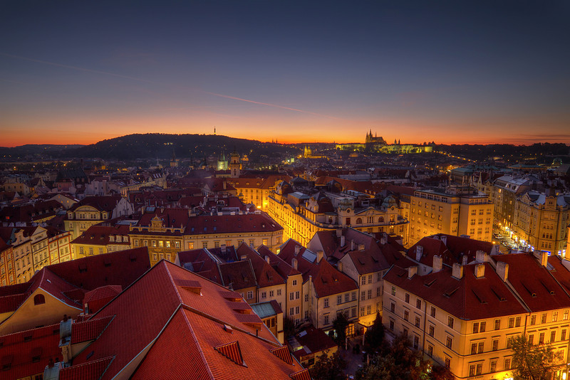 Streets of gold  This was my second visit to Prague this year, and for the second time, I had no nice clouds the whole weekend. Of course the booth days, when I was traveling, they were just stunning :) So I tried my best to work around it, taking as many photos as possible around sunset. This one is from the top of the Old Town hall tower right after the sun went down.   HDR from three shots, taken with Canon 7D with Sigma 10-20mm lens, from a tripod.