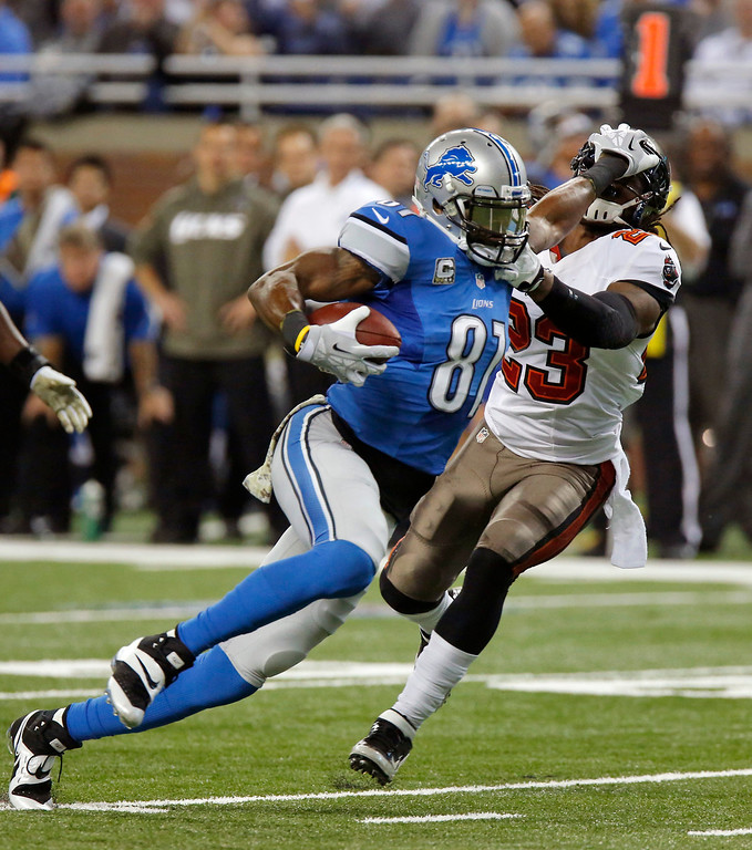 . Detroit Lions wide receiver Calvin Johnson (81) stiff arms Tampa Bay Buccaneers strong safety Mark Barron (23) after a 19-yard reception during the second quarter of an NFL football game in Detroit, Sunday, Nov. 24, 2013. (AP Photo/Duane Burleson)