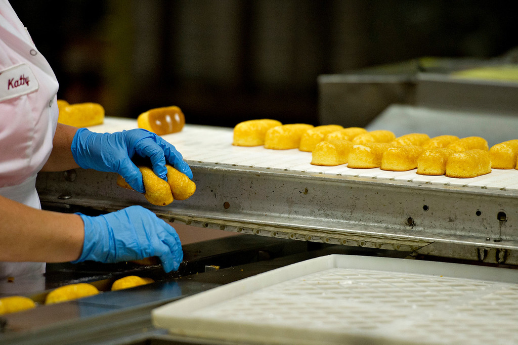 . An employee places freshly baked Hostess Brands LLC Twinkies snack cakes into a packaging machine at the company\'s bakery in Schiller Park, Illinois, U.S., on Monday, July 15, 2013.  Photographer: Daniel Acker/Bloomberg
