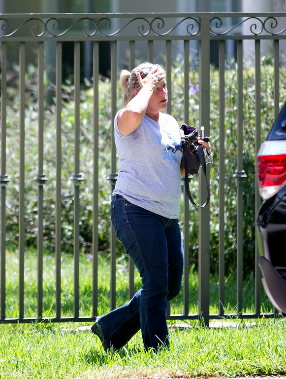 . An unidentified woman walks towards the home of the family of journalist Steven Sotloff, Tuesday, Sept. 2, 2014 in Pinecrest, Fla. An Internet video posted online Tuesday purported to show the beheading by the Islamic State group of Sotloff, who went missing in Syria last year. (AP Photo/Wilfredo Lee)