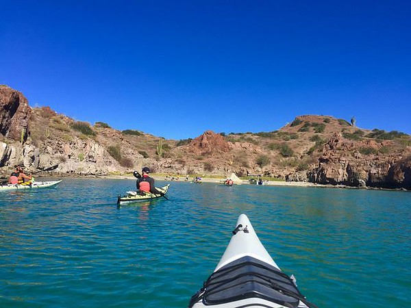 Kayaking on the blue water of Loreto Bay National Marine Park with desert landscape in the background.