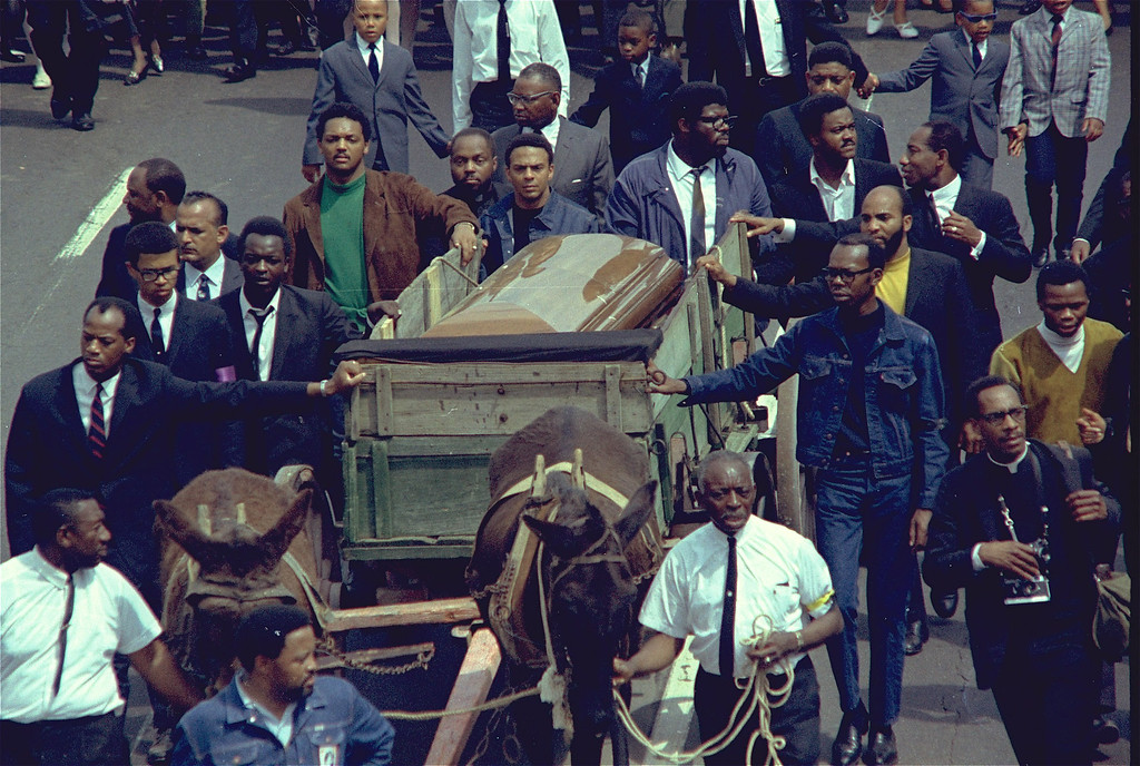 . A brace of plow mules drawing the farm wagon bearing the mahogany casket of Dr. Martin Luther King, Jr., along the funeral procession route in Atlanta, Ga., April 9, 1968.  Reverend Jesse Jackson, in green, and Andrew Young, at the left corner of the casket, are among some of the mourners.  (AP Photo)