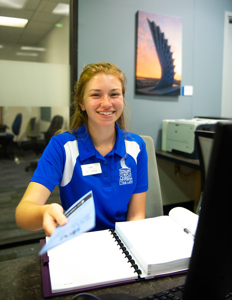 "Student worker Sally Moorman is always ready to help assist students with questions at the ""Ask Us"" desk on the first floor of the Mary and Jeff Bell Library."