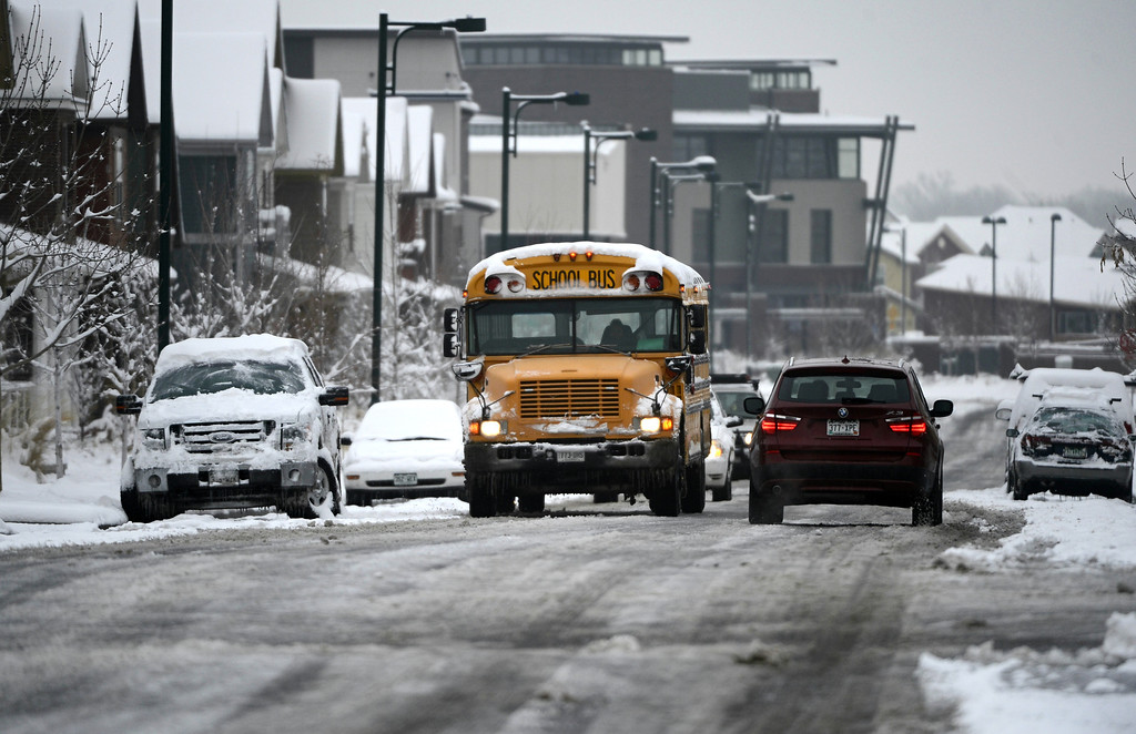 . A school bus and cars navigate a slushy 23rd Ave near Spruce St. in Denver, Tuesday morning, April 16th, 2013.  Andy Cross, The Denver Post