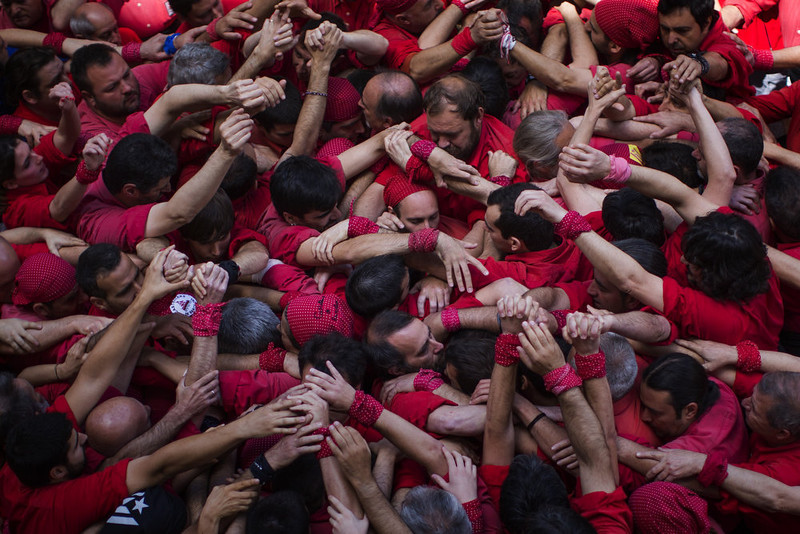 ". Members of the Castellers of Barcelona join their hands to start making their ""castell\"" or human tower in the Barcelona neighborhood of Gracia, Catalonia, Spain on Sunday May, 19 2013. A \""castell\"" is a human tower traditionally built during festivals in many places in Catalonia. At these festivals, several \""colles\"" or teams compete to build the most impressive towers they can. (AP Photo/Emilio Morenatti)"