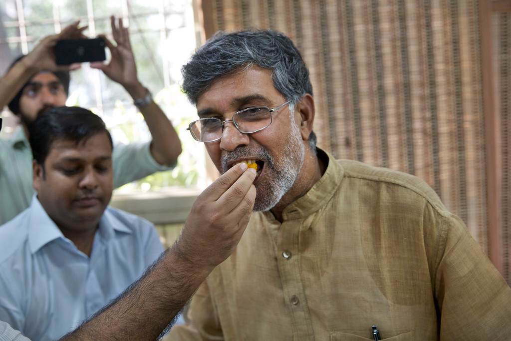 . An Indian man offers sweets to children\'s rights activist Kailash Satyarthi, right, as they celebrate after Satyarthi won the Nobel Peace Prize, at his office in New Delhi, India, Friday, Oct. 10, 2014. Malala Yousafzai of Pakistan and Satyarthi of India jointly won the Nobel Peace Prize on Friday, Oct. 10, 2014, for risking their lives to fight for children\'s rights. (AP Photo/Bernat Armangue)
