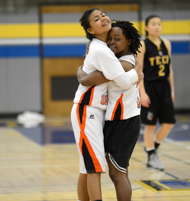 . McClymonds High\'s Romanalyn Inocencio (5), left, hugs Gabby Gaines (1) at the end of their game against Oakland Tech High in their Oakland Section high school girls basketball championship game played at Merritt College in Oakland, Calif. on Thursday, Feb. 28, 2013. (Dan Honda/Staff)