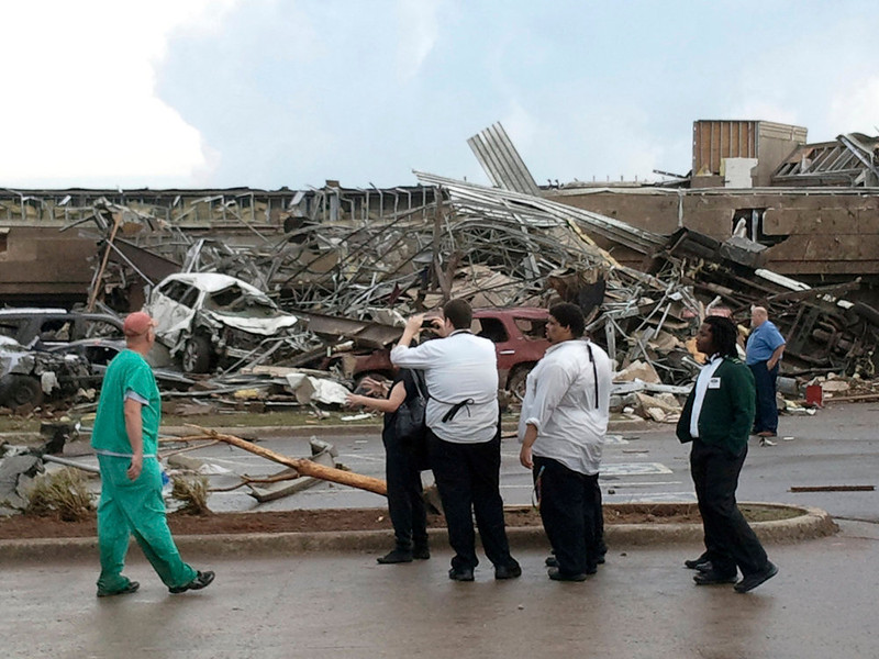 . People look at the destruction after a huge tornado struck Moore, Oklahoma May 20, 2013. A huge tornado with winds of up to 200 miles per hour devastated the Oklahoma City suburb of Moore on Monday, ripping up at least two elementary schools and a hospital and leaving a wake of tangled wreckage. At least four people were killed, KFOR television said, citing a reporter\'s eyewitness account, and hospitals said dozens of people were injured as the dangerous storm system threatened as many as 10 U.S. states with more twisters.  REUTERS/Gene Blevins