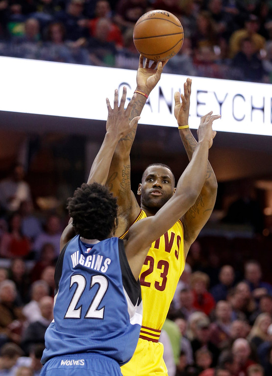 . Cleveland Cavaliers\' LeBron James (23) shoots over Minnesota Timberwolves\' Andrew Wiggins (22), from Canada, in the first half of an NBA basketball game Monday, Jan. 25, 2016, in Cleveland. (AP Photo/Tony Dejak)