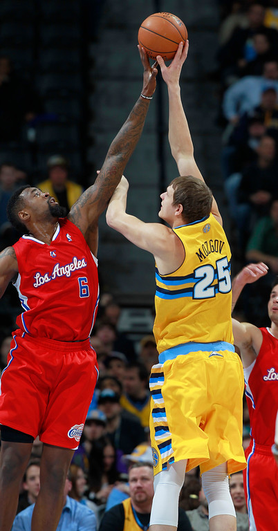 . Los Angeles Clippers center DeAndre Jordan, left, reaches up to block a shot by Denver Nuggets center Timofey Mozgov in the first quarter of an NBA basketball game in Denver, Monday, Feb. 3, 2014. (AP Photo/David Zalubowski)