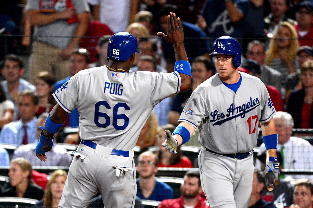 . Los Angeles Dodgers\' A.J. Ellis celebrates with Yasiel Puig as Puig brings in the first run as they play the Atlanta Braves in the first game of the playoffs Thursday, October 3, 2013 at Turner Field in Atlanta, Georgia. (Photo by Sarah Reingewirtz/Pasadena Star- News)