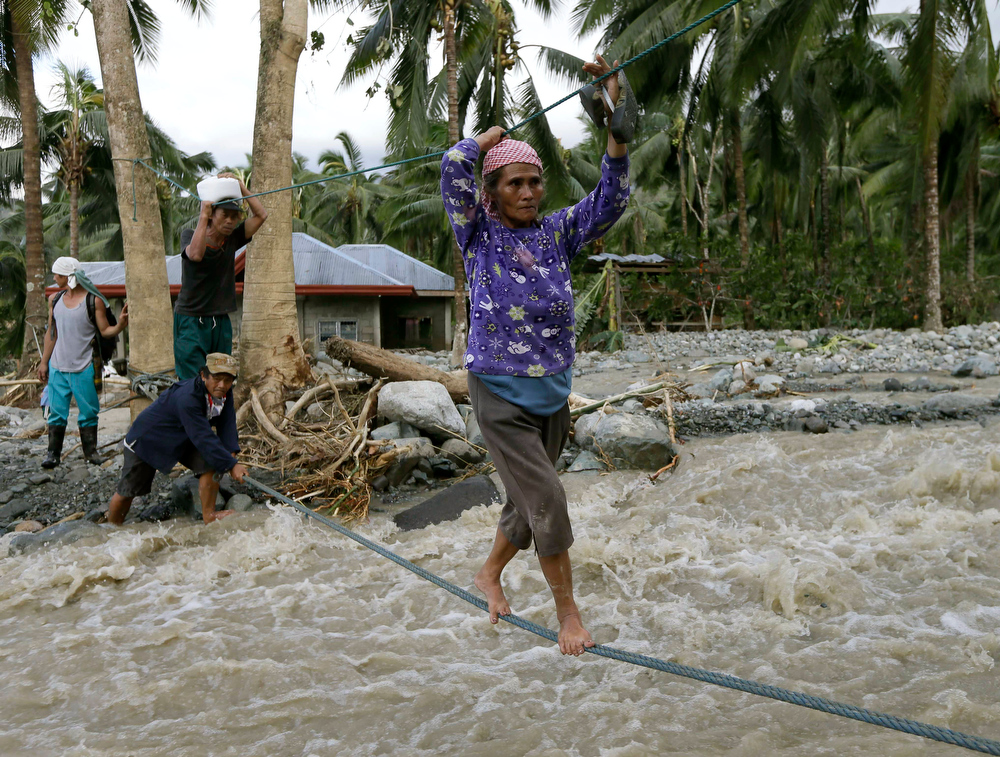 Description of . Residents cross a river using suspended ropes at Andap, New Bataan township, Compostela Valley in southern Philippines Wednesday, Dec. 5, 2012, a day after Typhoon Bopha made landfall. Typhoon Bopha, one of the strongest typhoons to hit the Philippines this year, barreled across the country's south on Tuesday, killing scores of people while triggering landslides, flooding and cutting off power in two entire provinces. (AP Photo/Bullit Marquez)