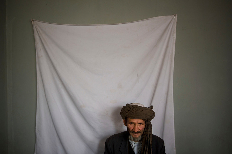 . An Afghan man waits to have his picture taken for his registration card on the last day of voter registration for the upcoming presidential elections outside a school in Kabul, Afghanistan, Tuesday, April 1, 2014. Elections will take place on April 5, 2014. (AP Photo/Anja Niedringhaus)