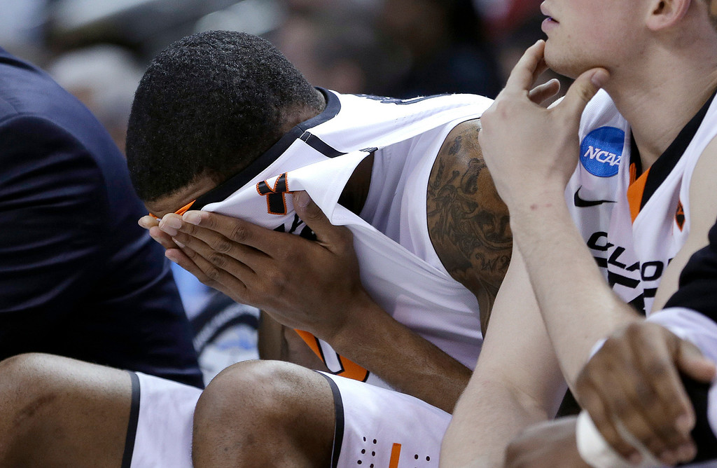 . Oklahoma State forward Michael Cobbins covers his face during the second half of a second-round game in the NCAA college basketball tournament against Oregon in San Jose, Calif., Thursday, March 21, 2013. Oregon won 68-55. (AP Photo/Ben Margot)